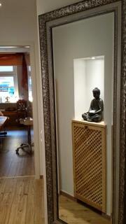 Wandfragment steinerne Buddhastatue auf Holzverkleidung
