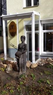 Außenbereich mit steinerner Statue Fensterfront