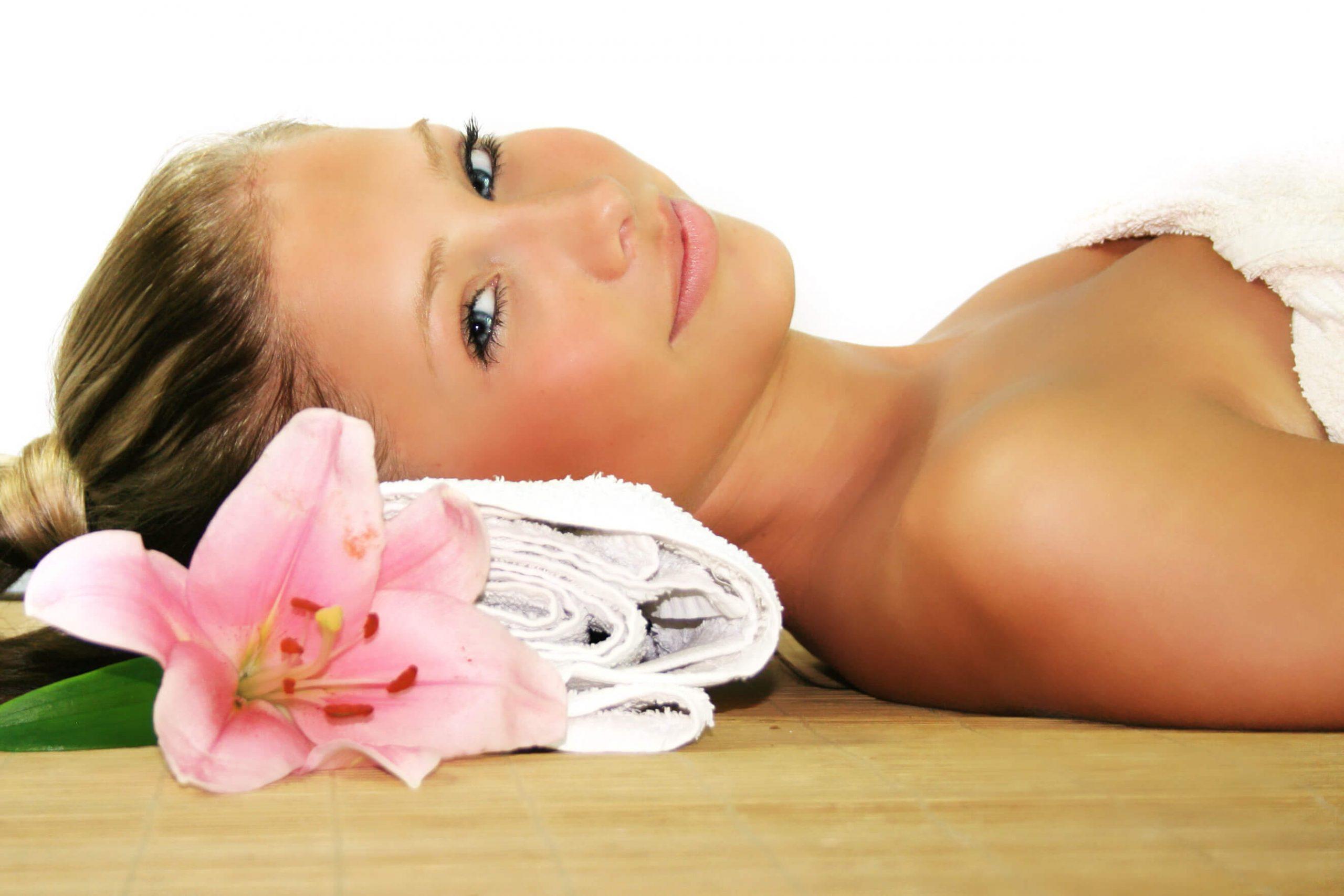 Junge Frau bei Kosmetikbehandlung mit rosafarbener Lotusblüte